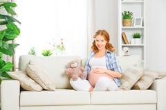 Lycklig gravid kvinna som hemma kopplar av med leksaknallebjörnen Royaltyfri Fotografi