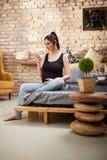 Lycklig gravid kvinna som hemma sitter royaltyfri fotografi
