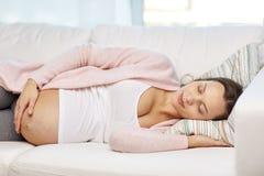 Lycklig gravid kvinna som hemma sover på soffan Royaltyfri Foto