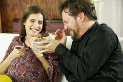 Lycklig gravid kvinna som skrattar med hållande glass för pojkvän Royaltyfria Foton