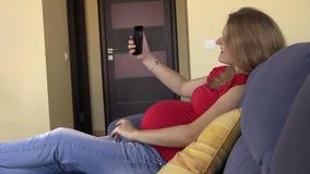 Lycklig gravid kvinnaforsselfie med smartphonen, bläddrandefoto arkivfilmer