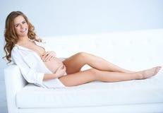Lycklig gravid ung kvinna på sofaen Royaltyfri Fotografi