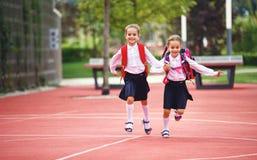 Lycklig grundskola för student för barnflickvänskolflicka arkivfoto