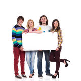 Lycklig grupp av studenter som rymmer det tomma banret Arkivbild