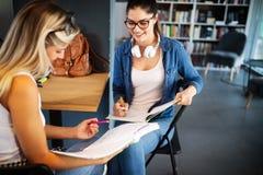 Lycklig grupp av studenter som tillsammans studerar och l?r i h?gskola royaltyfria foton