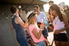 Lycklig grupp av unga vänner som har gyckel i sommar arkivfoto