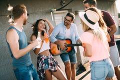 Lycklig grupp av unga vänner som har gyckel i sommar royaltyfri foto