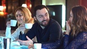 Lycklig grupp av vänner eller affärskollegor som tillsammans pratar och skrattar i stång Arkivbild