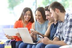 Lycklig grupp av vänner som kontrollerar åtskilliga apparater arkivbild