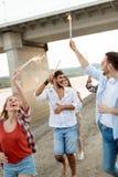 Lycklig grupp av vänner som tänder tomtebloss och tycker om frihet Arkivfoton