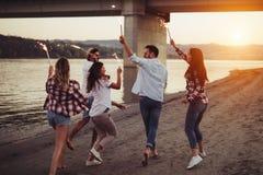 Lycklig grupp av vänner som tänder tomtebloss och tycker om frihet Royaltyfri Fotografi