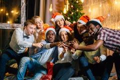 Lycklig grupp av vänner som trycker på glasesna med de arkivfoton
