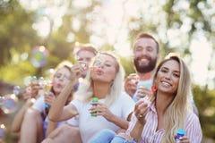 Lycklig grupp av vänner som utomhus blåser bubblor Arkivfoton