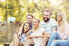 Lycklig grupp av vänner som utomhus tar selfie Royaltyfria Bilder