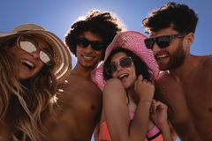Lycklig grupp av v?nner som har gyckel p? stranden i solskenet arkivfoto