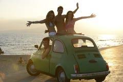 Lycklig grupp av vänner med den små bilen på strand Royaltyfri Foto