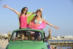 Lycklig grupp av vänner med den små bilen på strand Royaltyfria Bilder