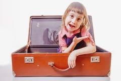 Lycklig gullig flicka för litet barn som sitter i resväska och väntande på lopp och affärsföretag på vit bakgrund fotografering för bildbyråer