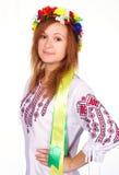 Lycklig gullig flicka i den ukrainska nationella dräkten och den ukrainska flaggan Arkivfoto