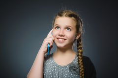 Lycklig gullig flicka med mobiltelefonen Isolerat på grå färg arkivfoton