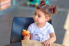 Lycklig gullig flicka p? ett kaf? som ?ter den nya gifflet, p? varm dag fotografering för bildbyråer