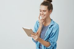 Lycklig gullig flicka som direktanslutet segrar lotterit för biljettbio som ser nöjt tillfredsställt digitalt le för minnestavlas royaltyfria bilder