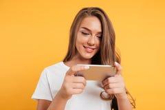 Lycklig gullig härlig lek för den unga kvinnan spelar vid mobiltelefonen royaltyfri foto