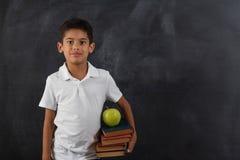 Lycklig gullig klyftig pojke med boken i hans hand Första gång till skolan tillbaka skola till Arkivbild