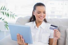 Lycklig gullig kvinna som köper direktanslutet genom att använda hennes minnestavlaPC Arkivfoton