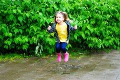 Lycklig gullig liten flickabanhoppning i pöl efter regn i sommar Royaltyfria Foton
