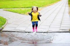 Lycklig gullig liten flickabanhoppning i pöl efter regn i sommar Arkivbild