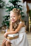 Lycklig gullig liten le flicka med julgåvaasken glada lyckliga ferier för jul Fotografering för Bildbyråer