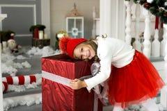 Lycklig gullig liten le flicka med julgåvaasken glada lyckliga ferier för jul Arkivfoton
