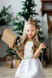 Lycklig gullig liten le flicka med julgåvaasken glada lyckliga ferier för jul Arkivfoto