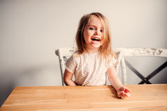 Lycklig gullig litet barnflicka som hemma spelar i kök Royaltyfria Bilder