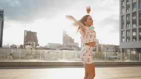 Lycklig gullig millenial hipsterflicka som har roligt utomhus- på stads- bakgrund för stadsgator Skönhetkvinnasnurr, banhoppning lager videofilmer