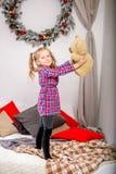Lycklig gullig ung flicka i ett rutigt blått-rött klänninganseende på sängen med en björn och att rymma för nalle den mot bakgrun arkivbild