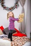 Lycklig gullig ung flicka i ett rutigt blått-rött klänninganseende på sängen med en björn och att rymma för nalle den mot bakgrun royaltyfri foto
