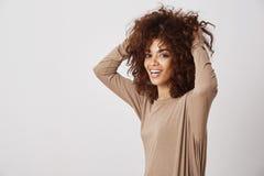 Lycklig härlig afrikansk flicka som ler trycka på hennes hår Vit bakgrund arkivfoto