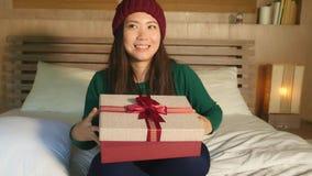 lycklig härlig asiatisk kinesisk kvinna i vinterhatten som sitter på spännande hållande julklapp för säng motta asken för gåva x- lager videofilmer