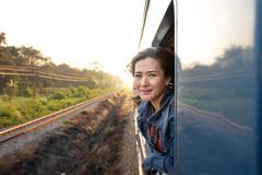 Lycklig härlig asiatisk kvinna som reser av drevet som ut ser från fönstret royaltyfri foto