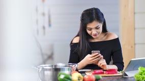 Lycklig härlig asiatisk kvinna som tycker om avbrottet genom att använda hemmastatt kök för smartphone stock video