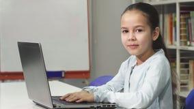 Lycklig härlig asiatisk liten flicka som ler, medan genom att använda bärbara datorn royaltyfri foto