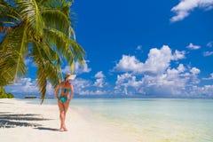 Lycklig härlig bekymmerslös kvinna som tycker om solsken på stranden Ung kvinna i sexig röd rosa bikini i den vita sandiga strand fotografering för bildbyråer