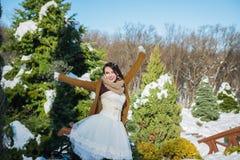 Lycklig härlig brud i en snöig vinterdag soligt väder stilfullt med bröllopbuketten som göras från den gjorda sörja-träd handen - Royaltyfri Fotografi