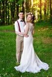 Lycklig härlig brud och brudgum som går på fält i solljus Fotografering för Bildbyråer