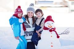 Lycklig härlig familjbyggnadssnögubbe i trädgården, vintertid, Royaltyfri Foto
