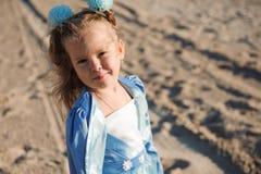 Lycklig härlig flicka i en blå klänning på stranden royaltyfria bilder