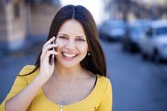 Lycklig härlig flicka i gul klänning som stannar till telefonen royaltyfria bilder