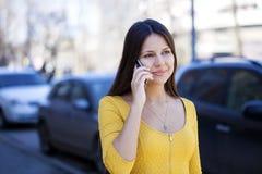Lycklig härlig flicka i gul klänning som stannar till telefonen arkivbild
